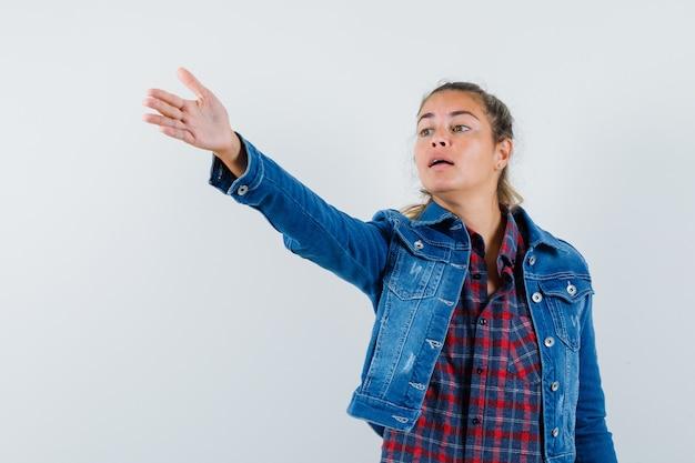 Junge frau in hemd, jacke, die hand streckt, um anweisungen zu geben und selbstbewusst, vorderansicht schauend.