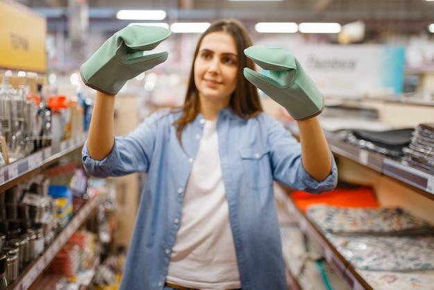 Junge frau in hitzebeständigen handschuhen, haushaltswarenladen. weibliche person, die haushaltswaren im markt kauft, dame im küchengeschirrversorgungsgeschäft