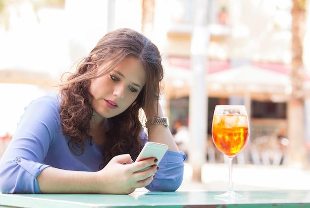 Junge frau in ihrer pause eine sms auf dem handy lesen