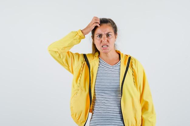 Junge frau in jacke, t-shirt kratzt den kopf und sieht nervös aus, vorderansicht.