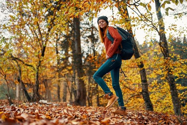 Junge frau in jeans und ein pullover mit einem rucksack auf ihrem rücken geht in den park im herbst in der natur, ansicht von unten. hochwertiges foto