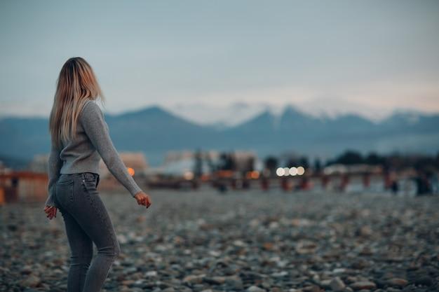Junge frau in jeans und pullover am kiesstrand der küste gekleidet.