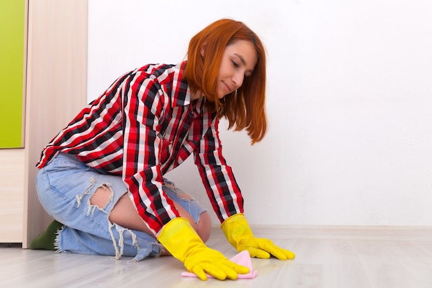 Junge frau in jeansgelben handschuhen und kariertem hemd wäscht den boden mit einem rosa lappen