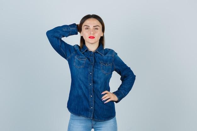 Junge frau in jeanshemd und jeans, die hand hinter kopf halten, während hand auf hüfte halten und selbstbewusst aussehen
