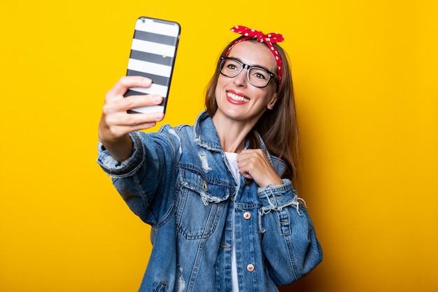 Junge frau in jeansjacke und brille hält ein telefon