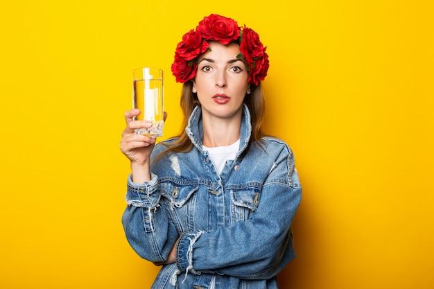 Junge frau in jeansjacke und einem kranz aus roten blumen auf ihrem kopf, der ein glas wasser an einer gelben wand hält.