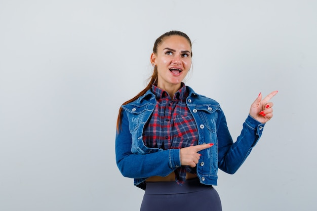 Junge frau in kariertem hemd, jacke, hose, die auf die rechte seite zeigt und glücklich aussieht, vorderansicht.