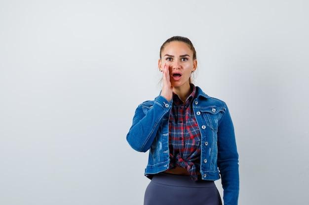 Junge frau in kariertem hemd, jeansjacke, die geheimnis erzählt und schockiert aussieht, vorderansicht.