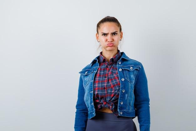 Junge frau in kariertem hemd, jeansjacke, die geschwollene wangen zeigt und verärgert aussieht, vorderansicht.