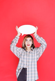 Junge frau in kariertem hemd mit ovaler infotafel