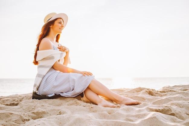 Junge frau in kleid und strohhut sitzt allein am leeren sandstrand bei sommersonnenuntergang am meer und lächelt. platz für nachricht.