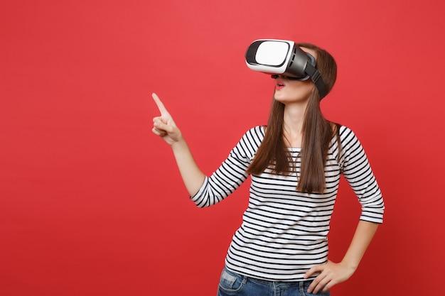 Junge frau in lässig gestreifter kleidung virtual-reality-brille, die mit dem zeigefinger beiseite schaut, isoliert auf leuchtend rotem wandhintergrund. menschen aufrichtige emotionen lifestyle-konzept. kopieren sie platz.