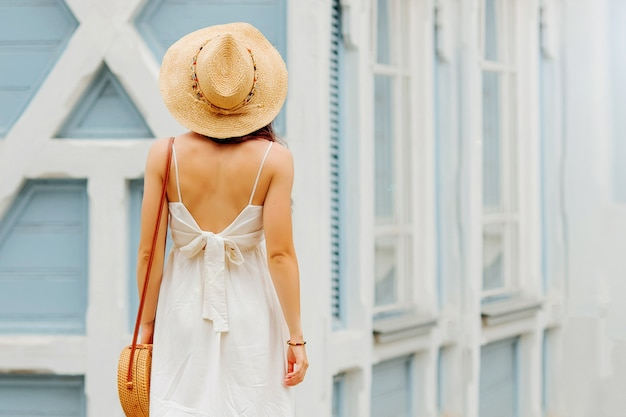 Junge frau in leichter sommerkleidung und strohhut mit bambushandtasche. sommerferienkonzept