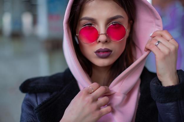 Junge frau in lila gläsern, die an haube festhalten