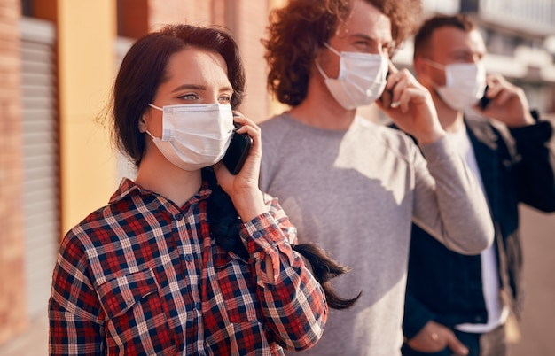 Junge frau in medizinischer maske, die wegschaut und smartphone-gespräche führt, während sie während der coronavirus-pandemie auf der stadtstraße in der nähe von männern steht