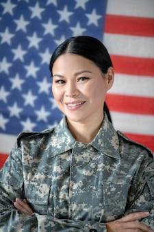 Junge frau in militäruniform mit der amerikanischen flagge