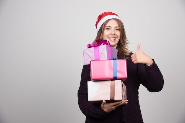 Junge frau in nikolausmütze mit geschenkboxen, die einen daumen nach oben zeigen.