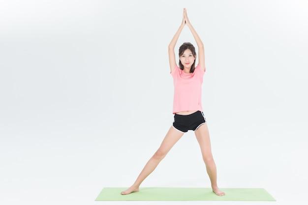 Junge frau in padmasana-pose, weißer studiohintergrund