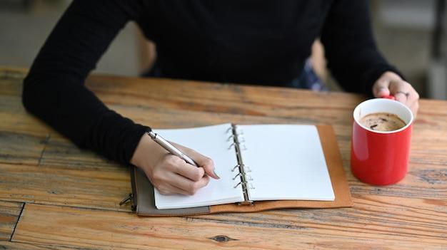 Junge frau in pullover planung arbeitsplan schreiben auf notebook.