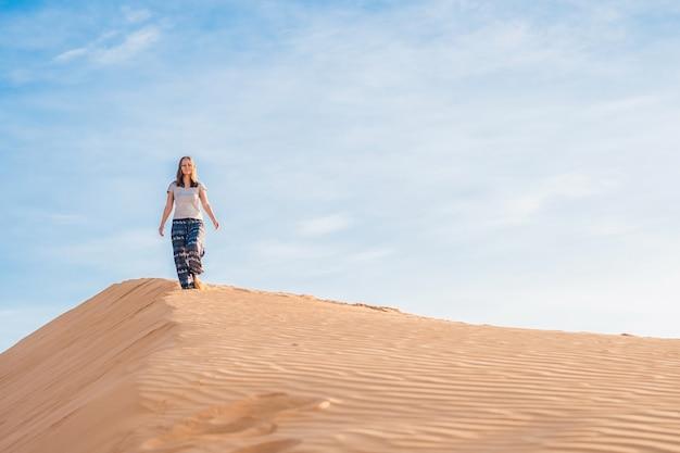 Junge frau in rad sandiger wüste bei sonnenuntergang oder morgengrauen