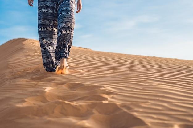 Junge frau in rad sandiger wüste bei sonnenuntergang