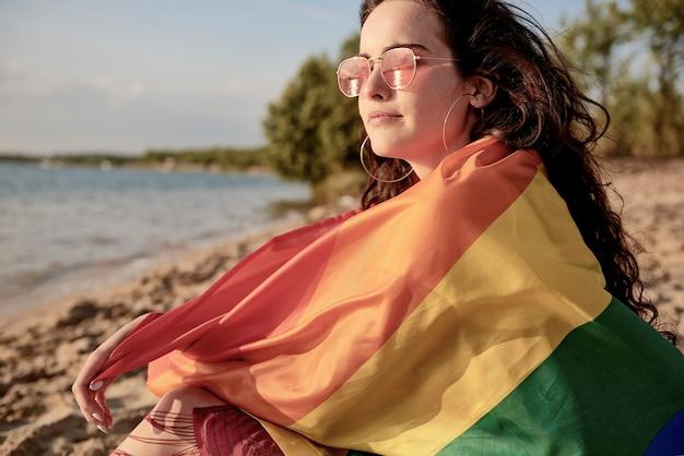 Junge frau in regenbogenfahne gehüllt am strand