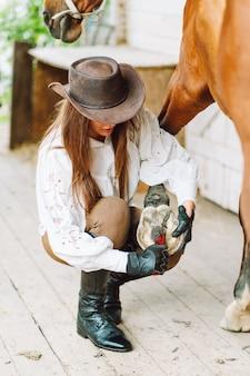 Junge frau in reitkleidung, die die hufe ihres braunen pferdes in einem stall säubert.