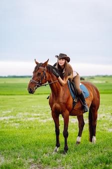 Junge frau in reitkleidung und hut, die auf einem braunen pferd auf der grünen wiese reitet