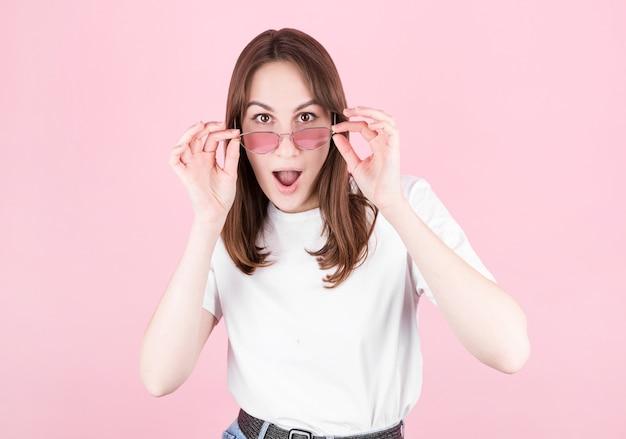 Junge frau in rosa brille ist sehr überrascht, in die kamera zu schauen und ihre brille zu senken
