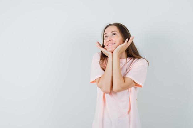 Junge frau in rosa t-shirt kissen gesicht auf ihren händen und suchen niedlich, vorderansicht.