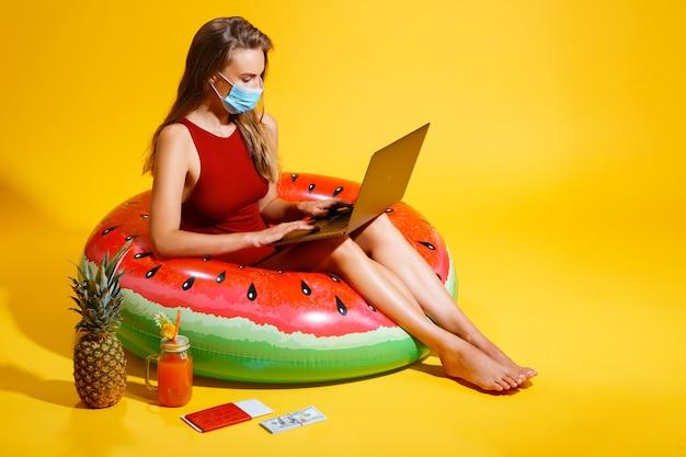 Junge frau in rotem badeanzug sitzt auf aufblasbarem kreis auf dem gelben hintergrund und trägt einen m...