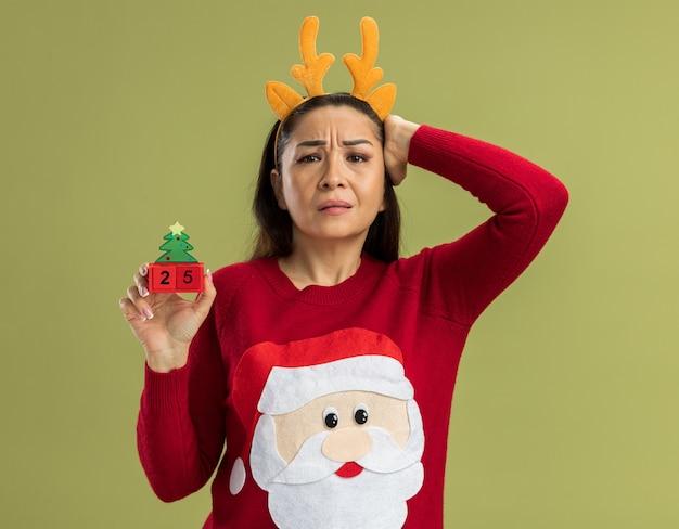 Junge frau in rotem weihnachtspullover, der lustigen rand mit hirschhörnern hält, die spielzeugwürfel mit datum fünfundzwanzig suchen, verwirrt mit hand auf ihrem kopf für fehler vergaß, über grünem hintergrund zu stehen