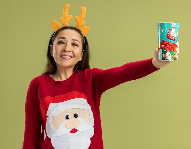 Junge frau in rotem weihnachtspullover mit lustigem rand mit hirschhörnern, die bunte pappbecher glücklich und fröhlich lächelnd über grüner wand stehen