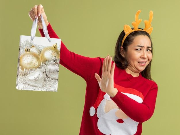 Junge frau in rotem weihnachtspullover mit lustigem rand mit hirschhörnern, die papiertüte mit weihnachtsgeschenk hält und sie mit unmut betrachtet, die hand über grüner wand stehend hält