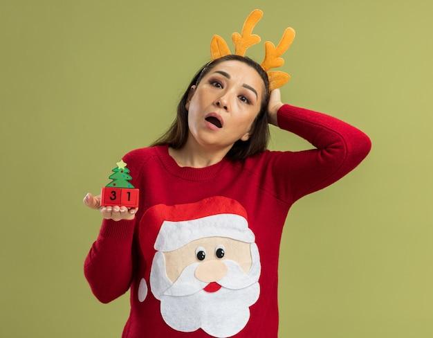 Junge frau in rotem weihnachtspullover mit lustigem rand mit hirschhörnern, die spielzeugwürfel mit neujahrsdatum zeigen, erstaunt über grüner wand stehend