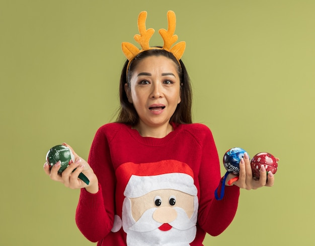 Junge frau in rotem weihnachtspullover mit lustigem rand mit hirschhörnern, die weihnachtskugeln halten überrascht und erstaunt über grüner wand stehend