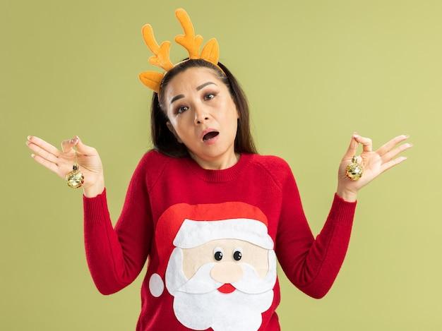 Junge frau in rotem weihnachtspullover mit lustigem rand mit hirschhörnern, die weihnachtskugeln halten, verwirrt, keine antwort über grüner wand stehen zu haben