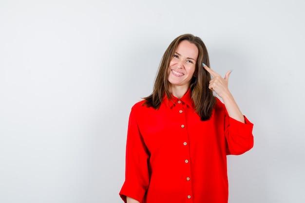 Junge frau in roter bluse, die auf ihren kopf zeigt und lustig aussieht, vorderansicht.