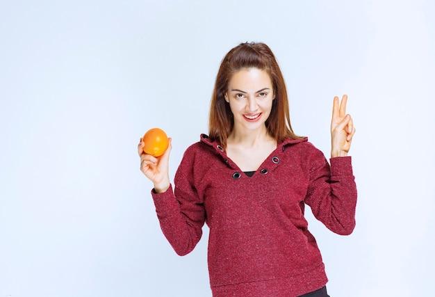 Junge frau in roter jacke, die eine orange hält und ein positives handzeichen zeigt