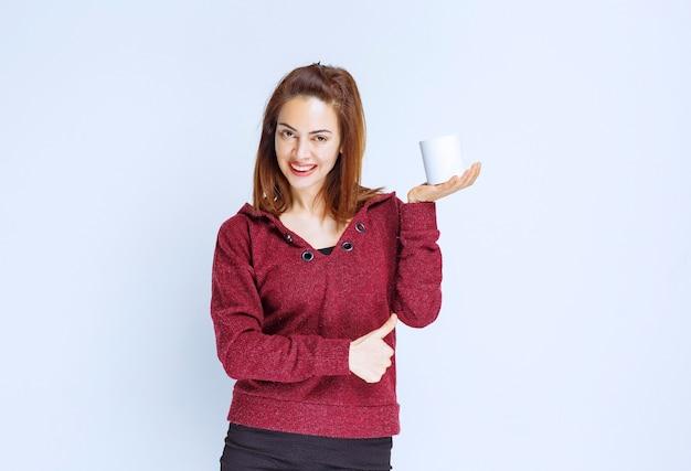 Junge frau in roter jacke, die eine weiße kaffeetasse hält und positives handzeichen zeigt