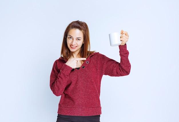 Junge frau in roter jacke, die eine weiße kaffeetasse hält