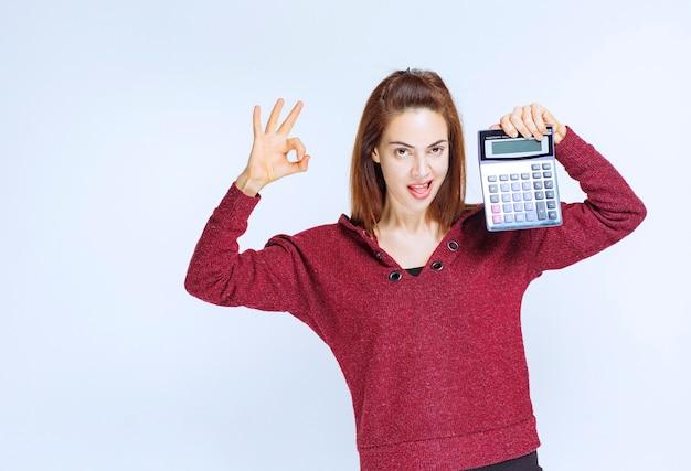Junge frau in roter jacke, die etwas auf einem blauen taschenrechner berechnet, das ergebnis und das ok-handzeichen zeigt
