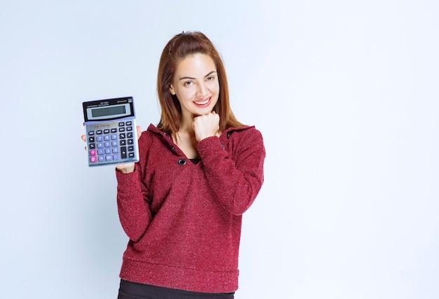 Junge frau in roter jacke, die etwas auf einem blauen taschenrechner berechnet und das endergebnis demonstriert