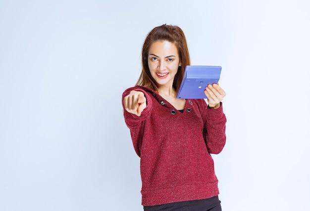 Junge frau in roter jacke, die etwas auf einem blauen taschenrechner berechnet und die person vor sich zeigt