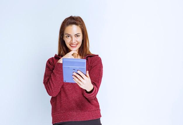 Junge frau in roter jacke, die etwas auf einem blauen taschenrechner berechnet und verwirrt aussieht