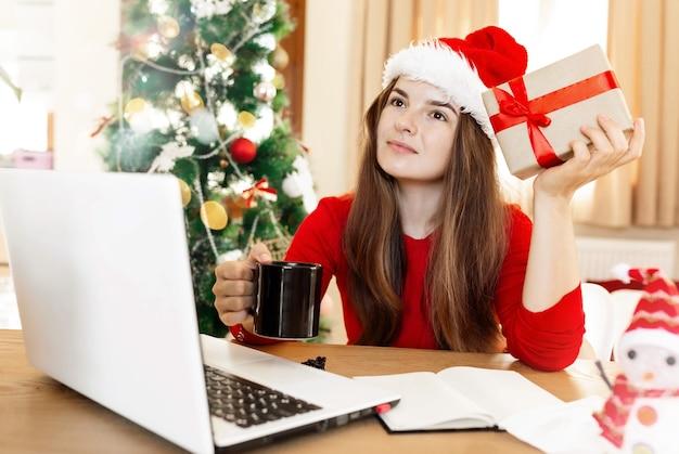 Junge frau in roter weihnachtsmütze, die an etwas denkt, das eine tasse mit getränk und geschenkbox hält?