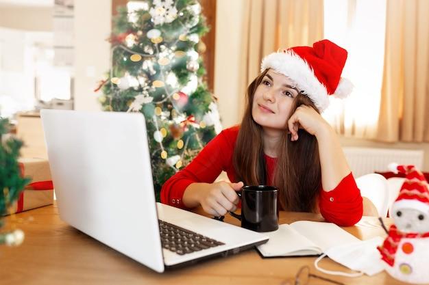 Junge frau in roter weihnachtsmütze träumt auf etwas, das eine tasse mit getränk hält und einen roten pullover sitzt