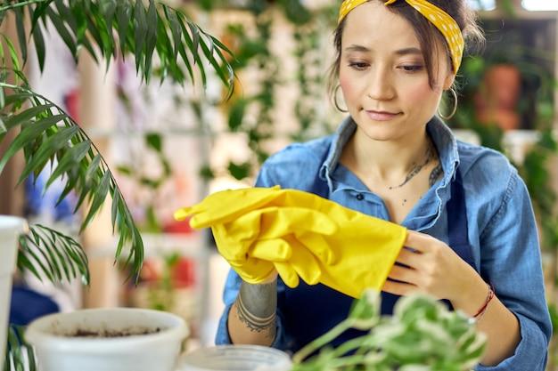 Junge frau in schürze, die gelbe gummihandschuhe anzieht, während sie sich auf das umpflanzen der pflanze vorbereitet