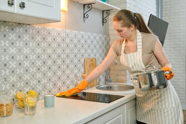Junge frau in schürzenhandschuhen, die die küche nach dem kochen reinigen