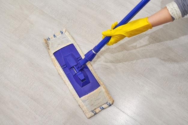 Junge frau in schützenden gelben gummihandschuhen mit flachem nassem mopp beim reinigen des bodens im haus.